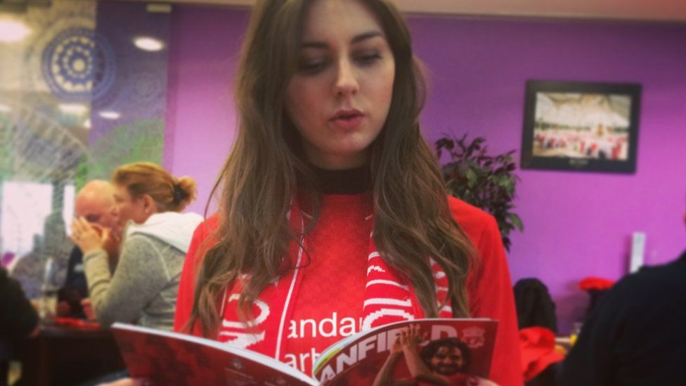 Hannah reading an Anfield brochure, wearing a Liverpool scarf