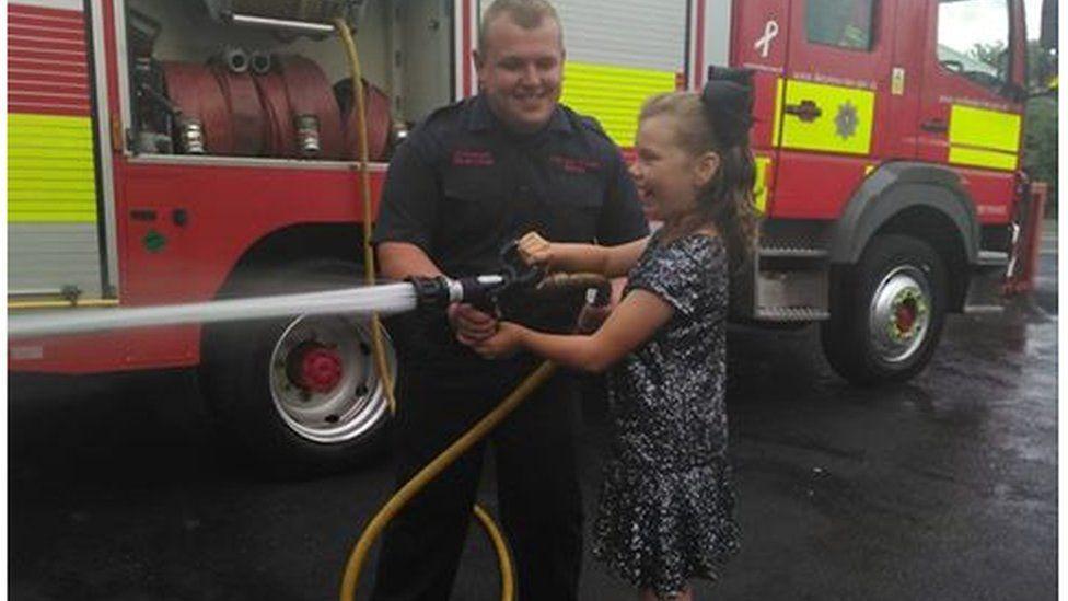 Kelcea holding a fire hose