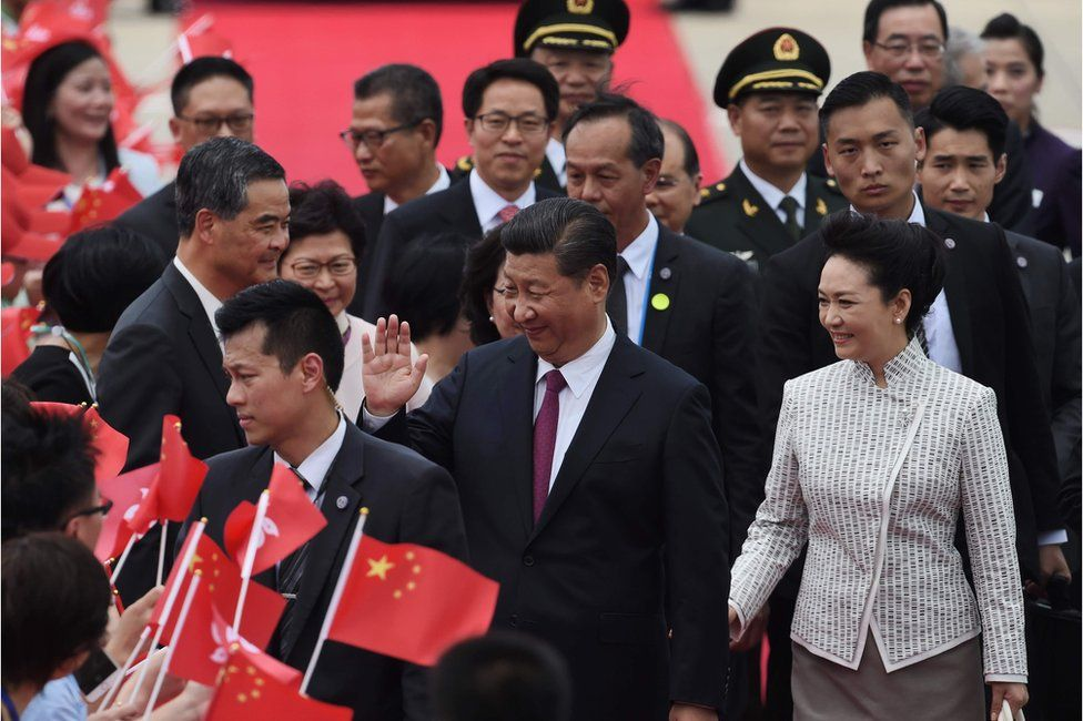 """China's President Xi Jinping (C) and his wife Peng Liyuan (front R) are greeted by Hong Kong""""s outgoing Chief Executive Leung Chun-ying (L) and wellwishers upon their arrival at Hong Kong""""s international airport on 29 June 2017"""