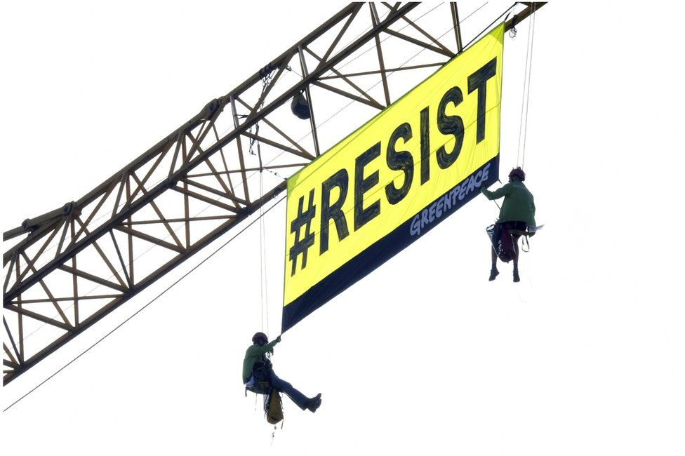 """Greenpeace activists unfurl a banner reading """"Resist"""" in Brussels, 25 May"""