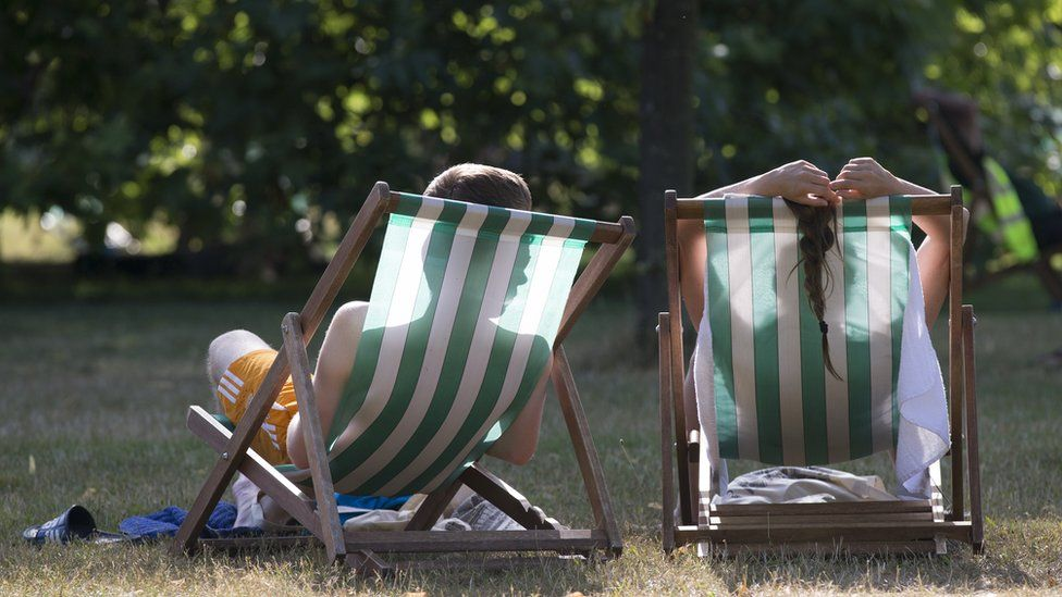 A couple relax on deckchairs in the warm weather in Hyde Park
