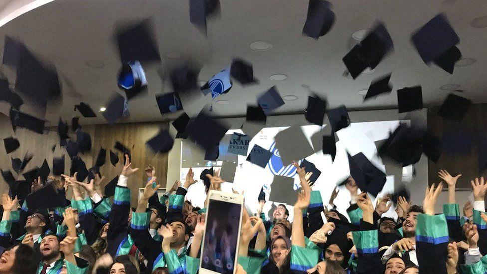 Graduates throw their mortar board hats in the air