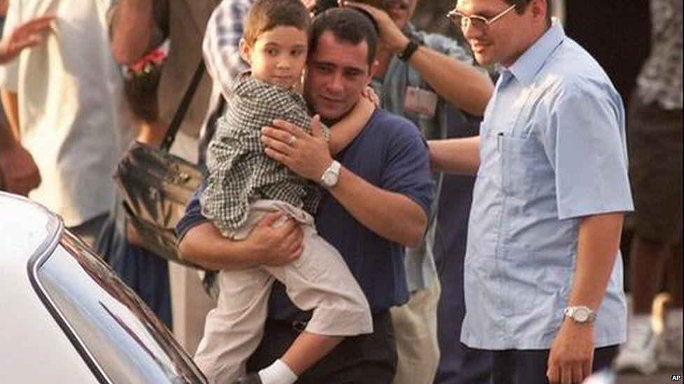 Juan Miguel Gonazalez carries his son Elian Gonzalez to a car as schoolmates wave upon their arrival to Havana's Jose Marti airport, Wednesday in June 2000