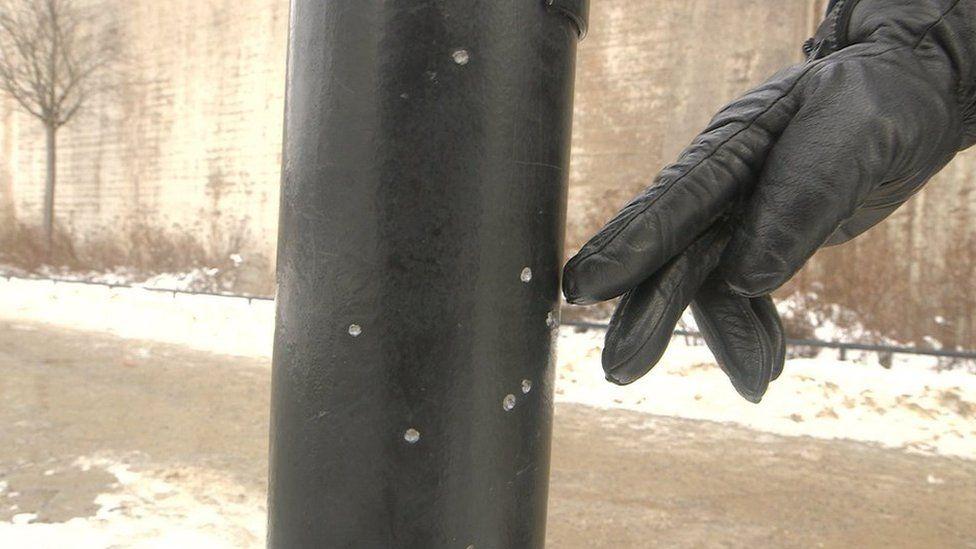 Shrapnel marks on a lamp post after a grenade explosion in Stockholm