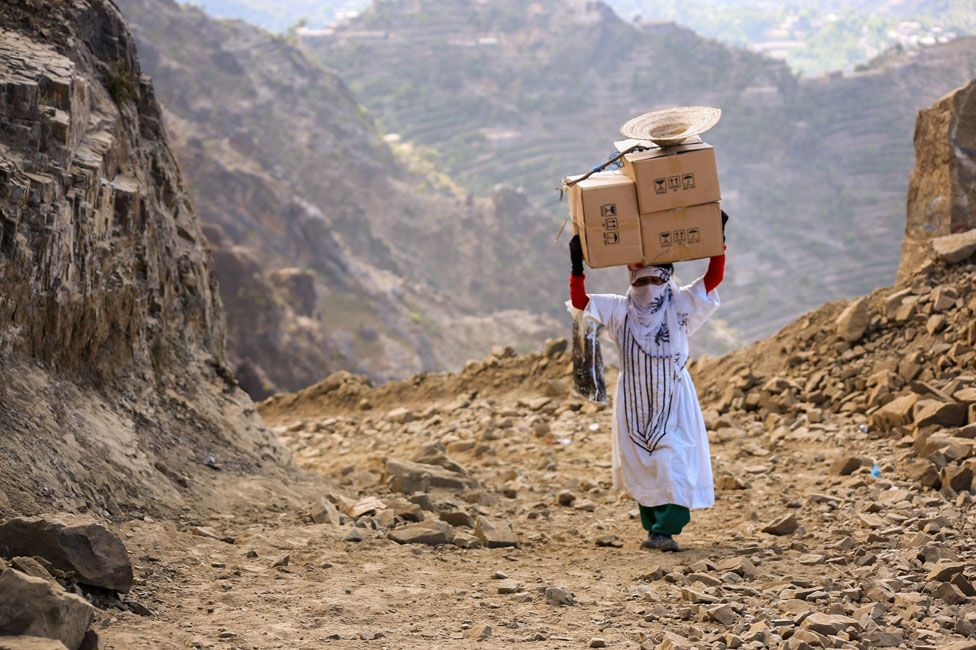 Woman carrying boxes over mountain paths to Taiz