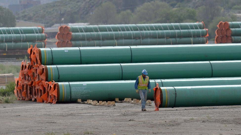 A workman walks past steel pipe to be used in the construction of the Trans Mountain expansion project