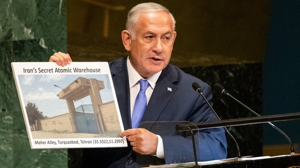 "Benjamin Netanyahu holds a picture of what he described as ""Iran's secret atomic warehouse"" in Tehran's Turquzabad district (27/09/18)"