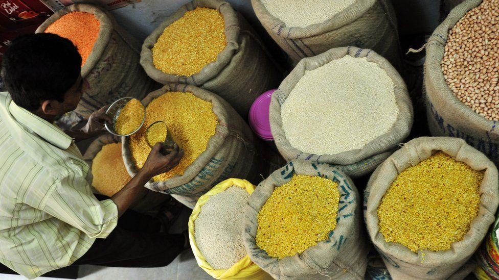 An Indian tradesman takes lentil samples at the wholesale market in Hyderabad, India