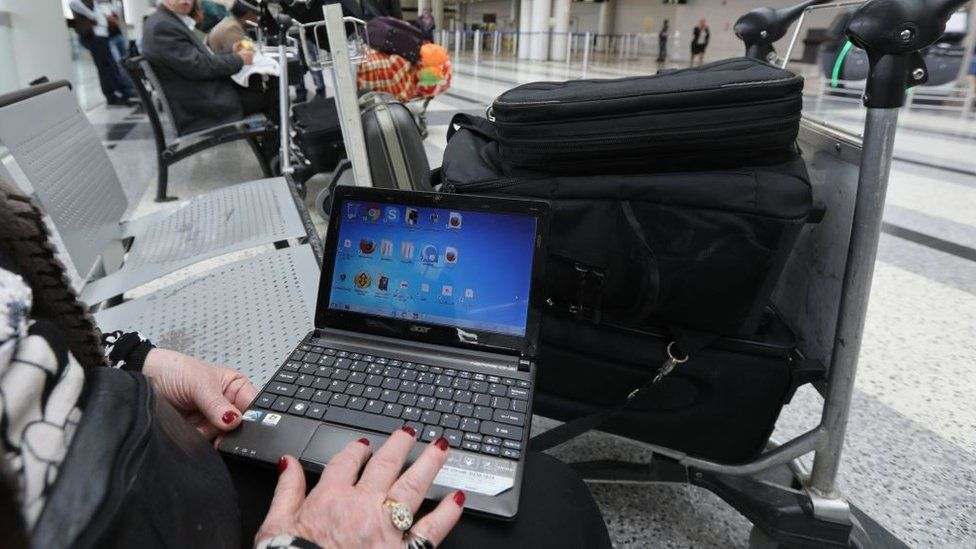 A Syrian woman travelling to the United States through Amman opens her laptop before checking in at Beirut international airport