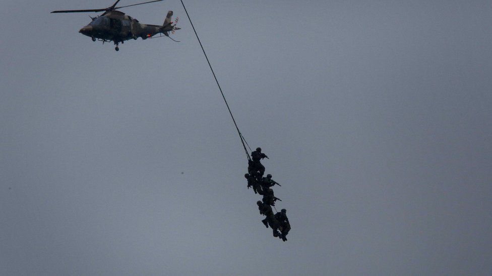 South African special forces soldiers perform an air stunt, hanging from a helicopter with weapons drawn in Durban - Tuesday 21 February 2017