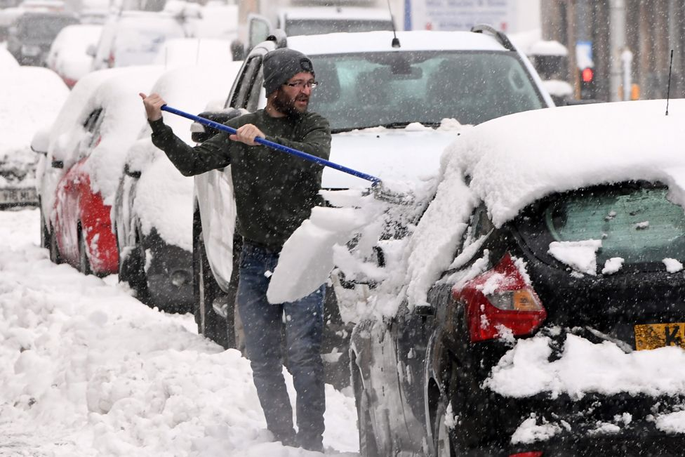 A man clears snow from his car in Auchterarder, Perth and Kinross, on 14 January 2021