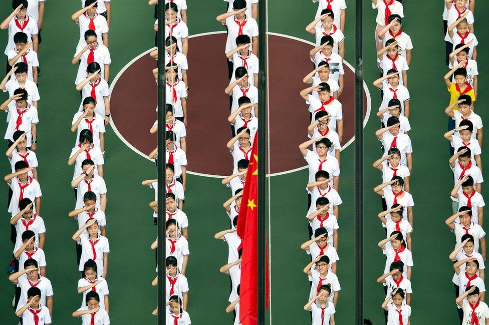 This aerial photo shows children lining up for a flag-raising ceremony.