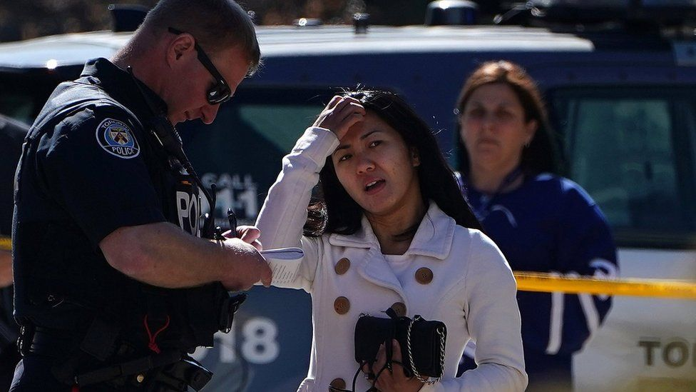 A witness speaks to a police officer at the scene of an incident where a van struck multiple people on Yonge Street in Toronto, Ontario, Canada April 23, 2018