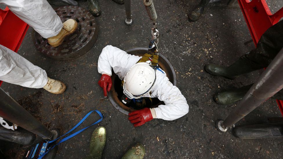 Thames Water sewer supervisor Vince Minney, emerges from a manhole in Whitehall after working in the Regent sewer in London on December 11, 2014