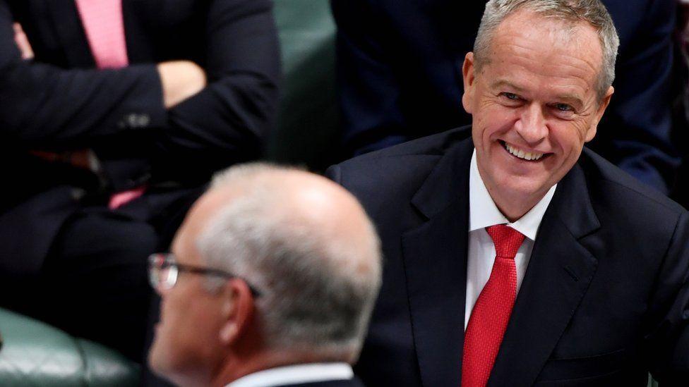Bill Shorten grins across the table at Scott Morrison in parliament