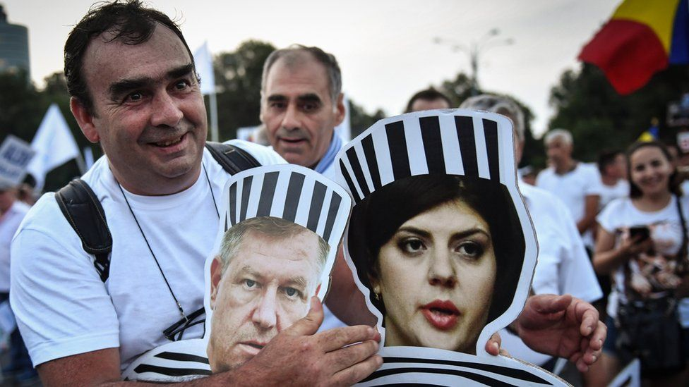 A pro government supporter holds cardboard cutouts showing Romanian President Klaus Iohannis and Chief Prosecutor of the National Anticorruption Directorate Laura Codruta Kovesi in Juna 2018