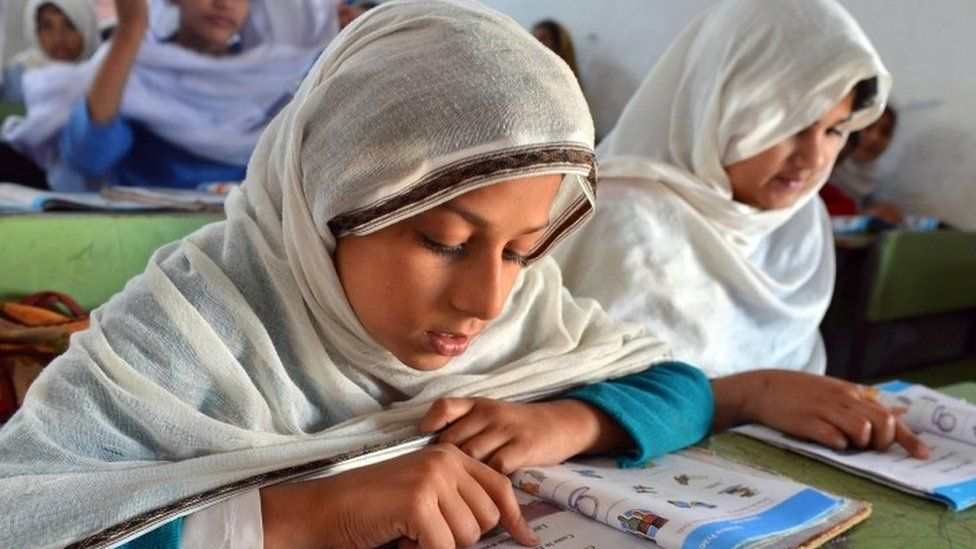 Pakistani female students attend a class at a government school in Peshawar (October 2012)