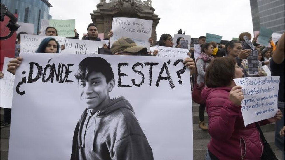 """Relatives and students hold posters reading """"Where is he?"""" as they protest against the disappearance of student Marco Antonio Sanchez, at the Angel de la Independencia monument in Mexico City on January 28, 2018"""