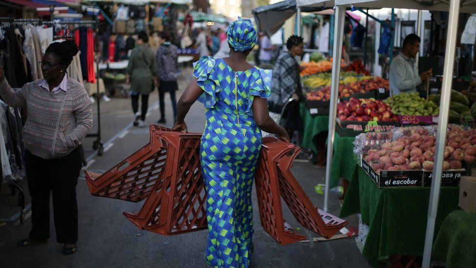 A trader carries trays at East Street Market in south London on September 2, 2017
