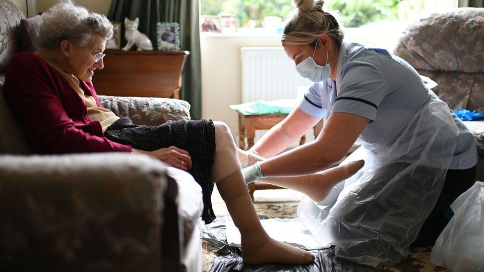a nurse Rebecca, wearing personal protective equipment (PPE), changes the dressings on the legs of an elderly woman during a home visit.