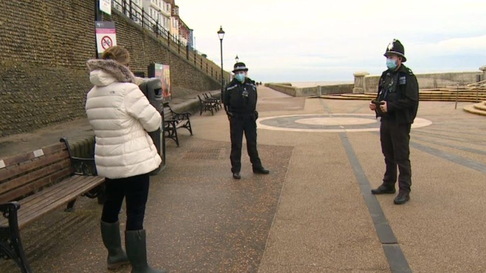 Two police officers stop a member of the public in Cromer, Norfolk.