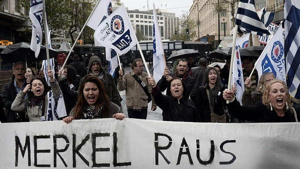 People demonstrate by a police blockade during a demonstration against the visit of the German Chancellor Angela Merkel in Athens on April 11, 2014