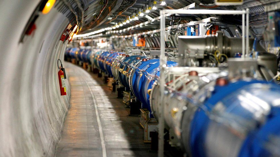 An image shows high-tech machinery in a long array, almost like a very large tube, running through a concrete tunnel, with a staggering array of cables and gleaming industrial machinery connected to the tube