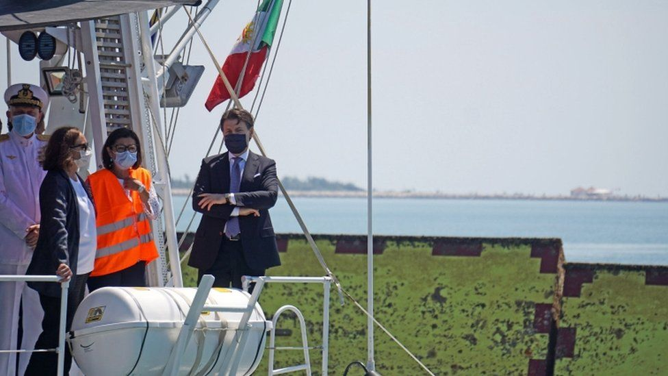 Italian Prime Minister Giuseppe Conte stands on the deck of a boat of the Italian Coast Guard