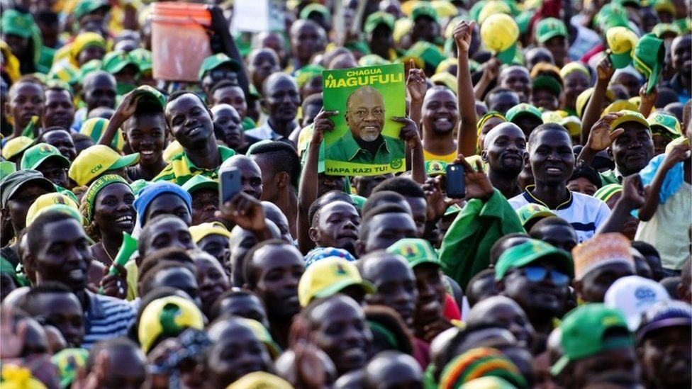 A man holds up a poster of presidential candidate John Magufuli during a ruling Chama Cha Mapinduzi (CCM) rally in Dar es Salaam, Tanzania, on October 21, 2015