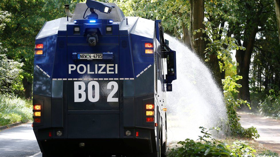 A police water cannon is used to hose trees in Bochum, Germany, 31 July 2018