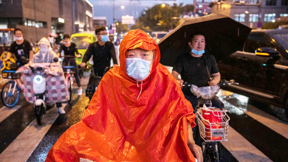 An elderly man wears a mask and a raincoat as waits on his scooter with others to cross at a traffic light during a rainstorm on 8 September 2021 in Beijing, China