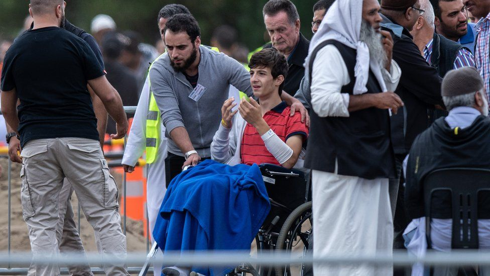 Zaid Mustafa in a wheelchair at the funeral for his father and brother