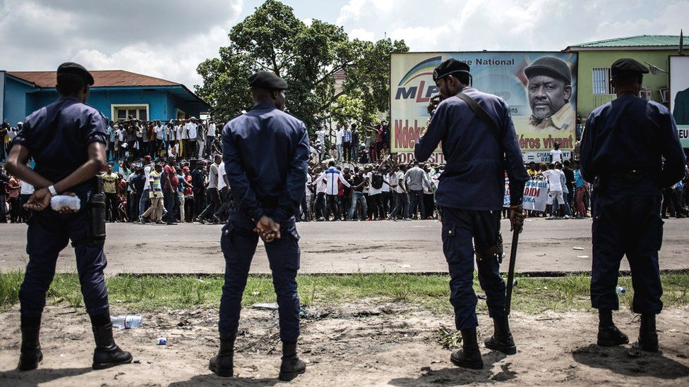 Police stand in front of supporters of Democratic Republic of Congo opposition leader and presidential candidate Martin Fayulu as they take part in a protest to contest presidential election results in Kinshasa on 11 January 2019