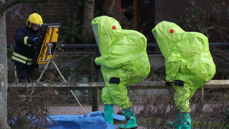 Investigators in hazmat suits walk near where Sergei and Yulia were found