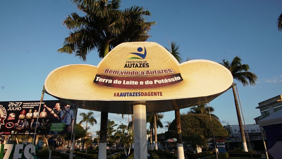 """Photo of a sign reading """"Welcome to Autazes, Land of Milk and Potassium"""""""