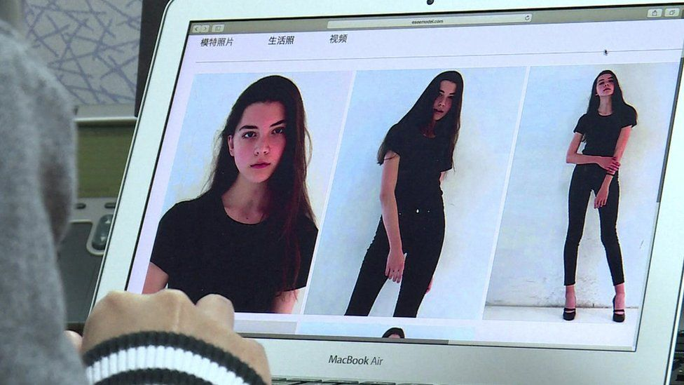 The photo shows a laptop screen with three images of the model, in a black top and trousers in various poses