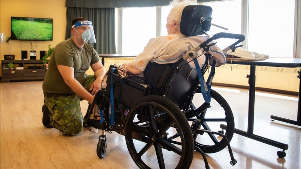 A Canadian soldier aids a senior citizen at a long-term care centre in Montreal, Quebec on 10 May