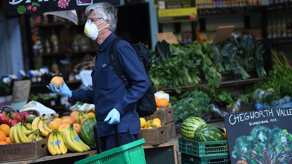 A masked man shops for oranges at Borough Market in London, Britain, 05 June 2020. From June 01 the British government has stated that some business including open air markets are allowed to trade.