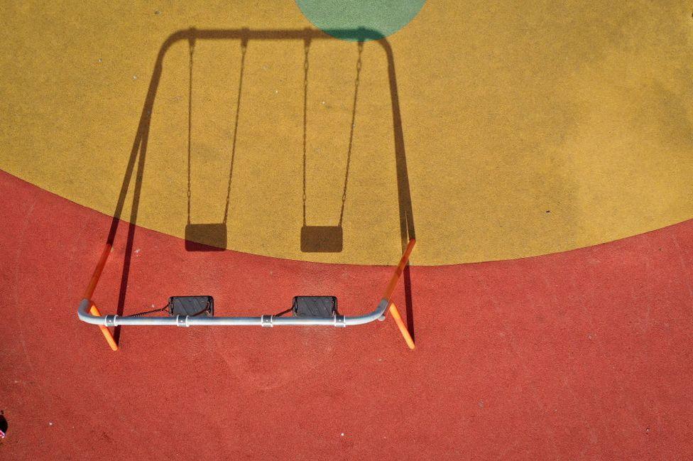 A children's playground lays dormant