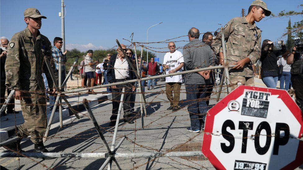 Cypriot soldiers remove a barbered-wire fence at a newly opened checkpoint in Dherinia, Cyprus November 12, 2018.