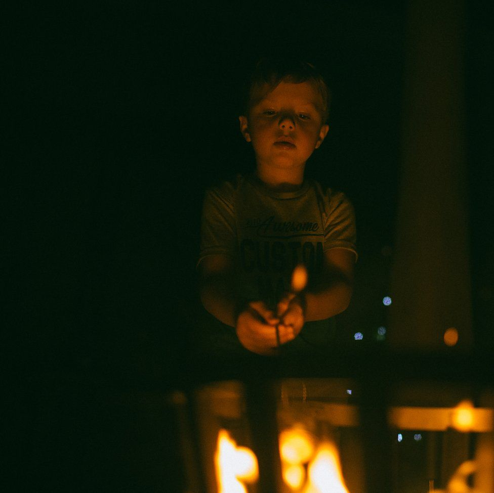 An image of a boy roasting food over a fire