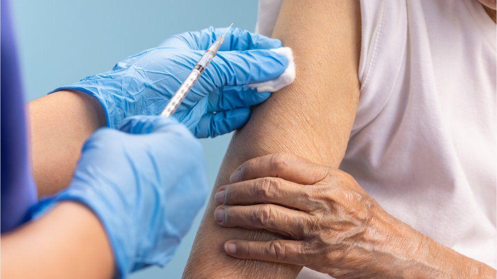 Nurse vaccinating an older woman