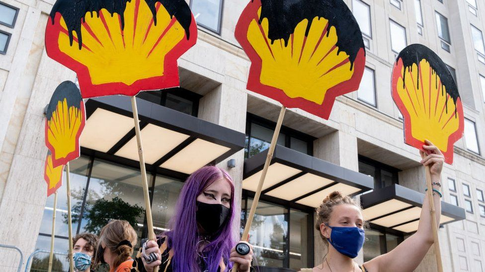 Protesters hold placards with the Shell logo drenched in oil in London, September 2020