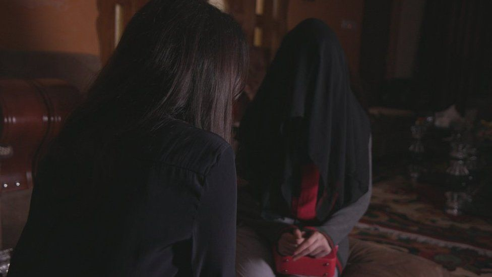 The BBC's Nawal al-Maghafi speaks to a girl who has hidden her identity under a black cloth