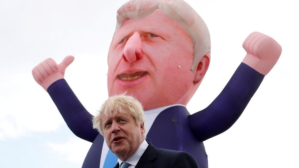 Prime Minister Boris Johnson with an inflatable figure depicting him in the background