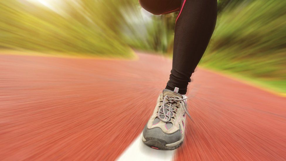 Close-up of running legs on a road surface