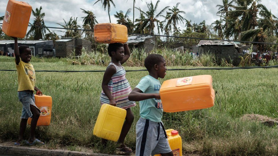 Children holding empty plastic containers in Mozamique