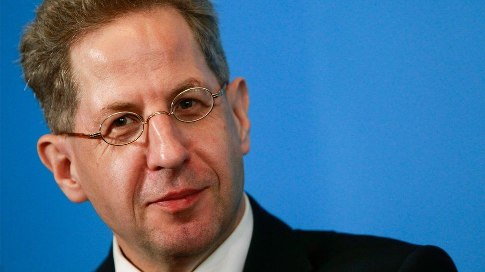 Hans-Georg Maassen looks on during a press conference, surrounded by a bright blue background