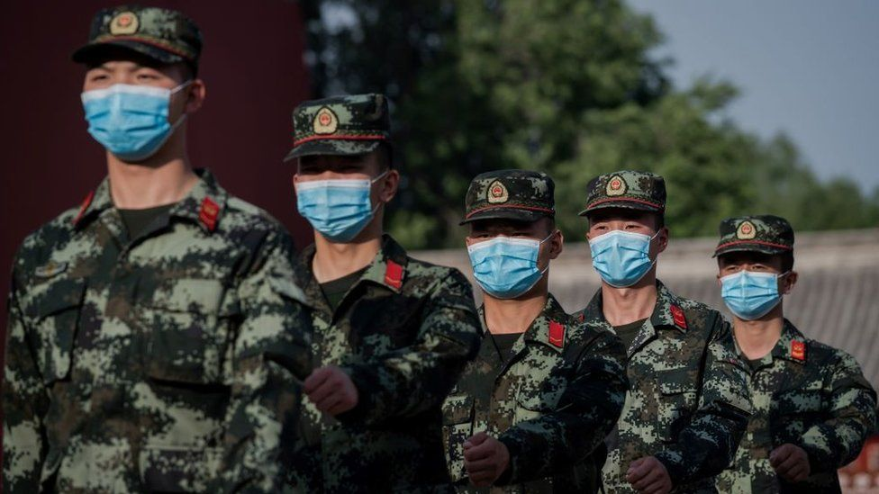 PLA troops march with face masks on in Beijing