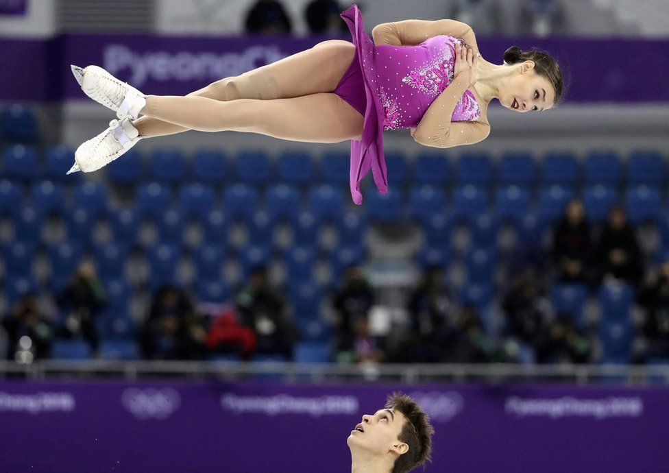 Ice skater Anna Duskova spins in the hair horizontally as her partner Martin Bidar looks up at her